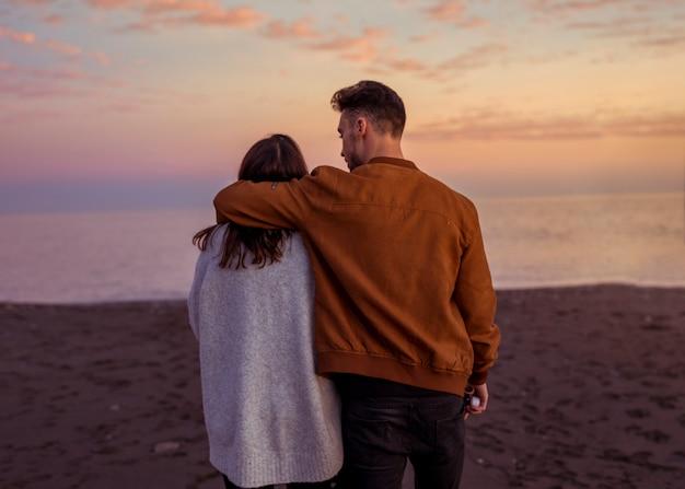 Jong koppel knuffelen op zanderige kust in avond