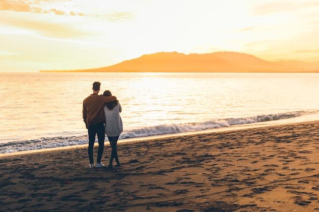 Jong koppel knuffelen op zee kust