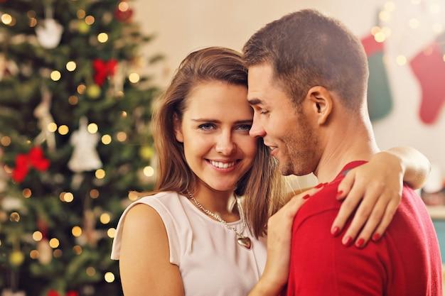 Jong koppel knuffelen over kerstboom