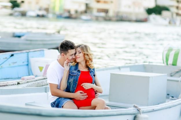 Jong koppel knuffels en ontspannen op dok in de buurt van boot, op zonnige zomerdag. vrouw en man in modieuze kleding staat in de buurt van luxejacht. luxe leven concept. paar verliefd reizen, huwelijksreis tijd.