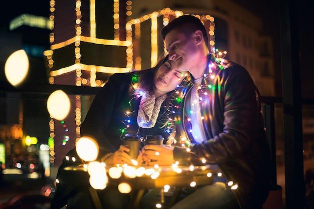 Jong koppel kussen en knuffelen buiten in nacht straat in de kersttijd