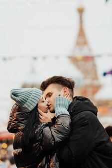 Jong koppel kussen en knuffelen buiten, op straat in de kersttijd