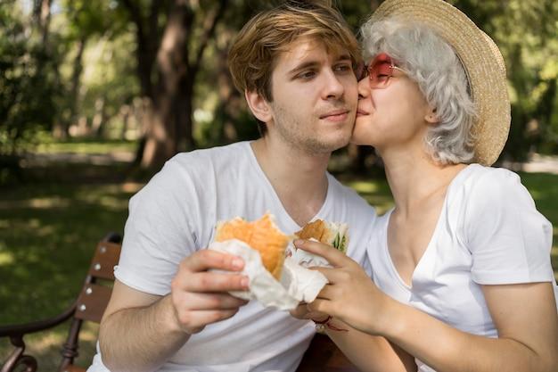 Jong koppel kussen tijdens het eten van hamburgers in het park