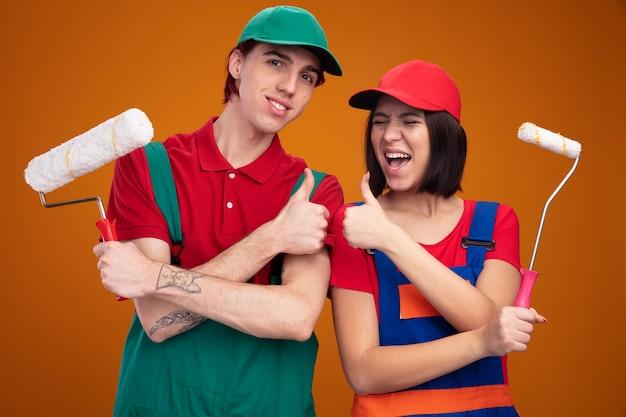 Jong koppel lachende man en vrolijk meisje in bouwvakker uniform en pet met verfroller duim omhoog kerel kijken camera meisje met gesloten ogen geïsoleerd op oranje muur