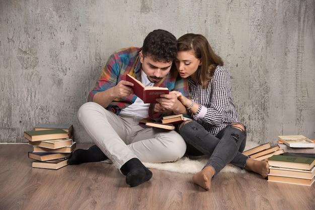 Jong koppel lezen van een interessant boek zittend op de vloer