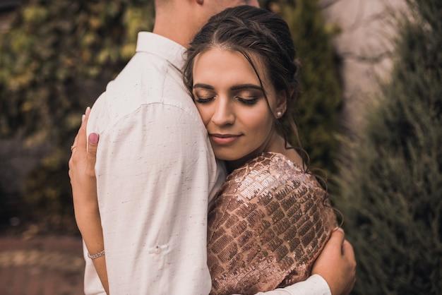 Jong koppel liefhebbers man en vrouw in feestelijke modieuze kleding knuffelen. licht casual kapsel voor vrouwen met een permanent. zomer natuur buiten achtergrond.