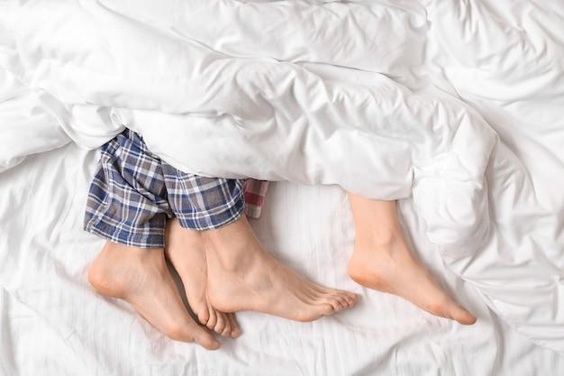 Jong koppel liggend in bed, bovenaanzicht