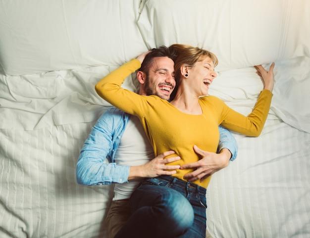 Jong koppel liggend in bed plezier lachen terwijl samen kietelen. mensen verliefd glimlachend thuis in de slaapkamer