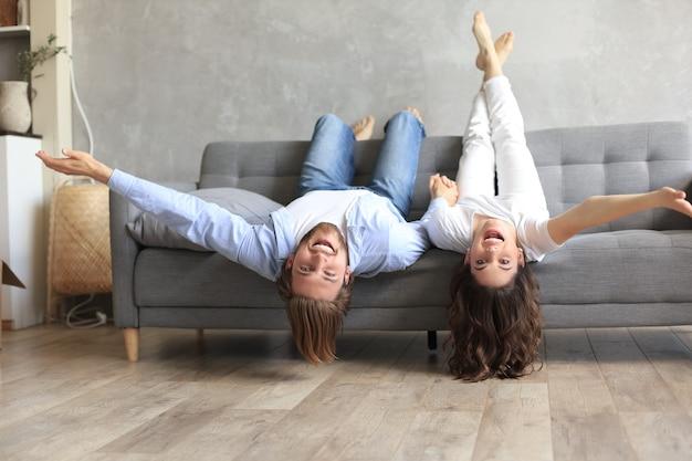 Jong koppel liggend op de bank met hoofden ontspannen ondersteboven glimlachend naar de camera in de woonkamer op de verhuisdag.