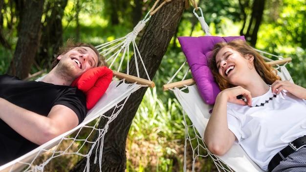 Jong koppel liggend op hangmatten kijken elkaar glimlachend aan
