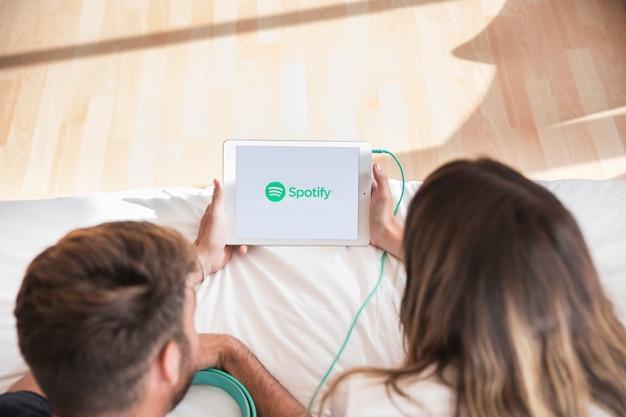 Jong koppel luisteren muziek met spotify-app