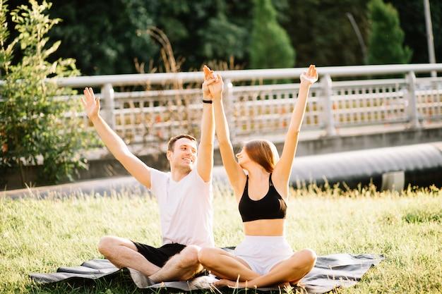 Jong koppel man en vrouw aan het sporten, yoga op het gazon van de stad, samenzijn in de zomeravond