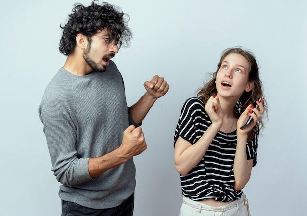 Jong koppel man en vrouw, afkeurende man met gebalde vuisten kijken naar verrast meisje dat smartphone staande houden op witte achtergrond