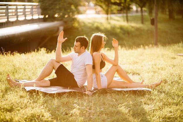 Jong koppel man en vrouw doen aan sport, yoga op het gazon van de stad, zomeravond samen