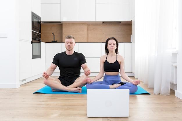Jong koppel man en vrouw doen fitness thuis online met behulp van laptop, online doen met trainer op verdieping thuis sporten