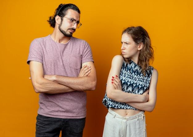 Jong koppel man en vrouw fronsen kijken elkaar staande over oranje achtergrond