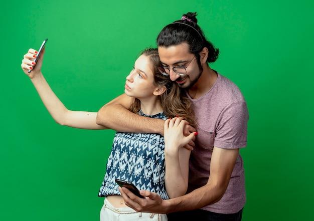 Jong koppel man en vrouw, gelukkig man knuffelen zijn vriendin terwijl ze het nemen van foto van hen met behulp van smartphone staande op groene achtergrond