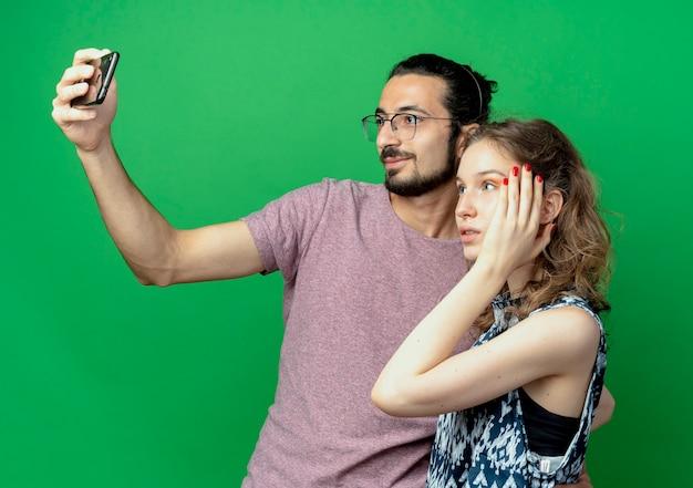 Jong koppel man en vrouw, gelukkig man nemen foto van hen met behulp van zijn smartphone staande op groene achtergrond