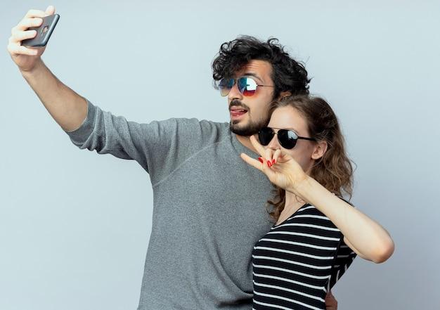 Jong koppel man en vrouw gelukkig verliefd, gelukkig man nemen foto van hen met behulp van smartphone staande over witte muur