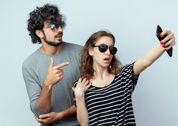 Jong koppel man en vrouw gelukkig verliefd, gelukkige vrouw nemen foto van hen met behulp van smartphone staande op witte achtergrond