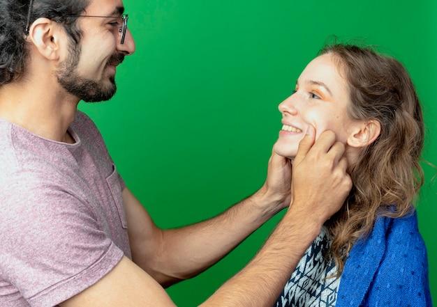 Jong koppel man en vrouw gelukkig verliefd, man knijpen de wangen van zijn vriendin staande over groene muur