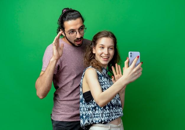 Jong koppel man en vrouw, gelukkige vrouw nemen foto van hen met behulp van haar smartphone staande op groene achtergrond