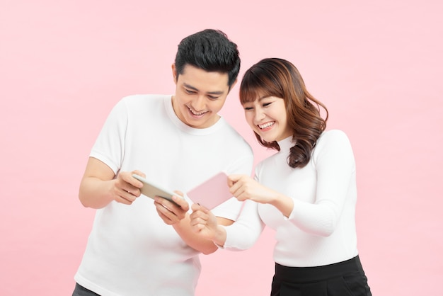 Jong koppel man en vrouw gluren naar elkaars mobiele telefoons houden in handen geïsoleerd over roze achtergrond