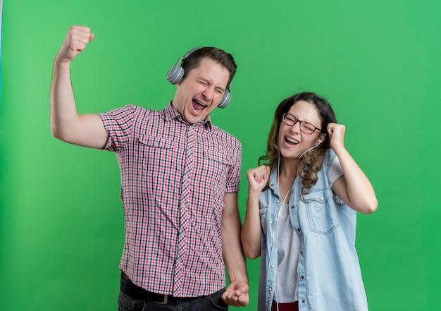 Jong koppel man en vrouw in casual kleding met koptelefoon blij en opgewonden genieten van favoriete muziek over groen