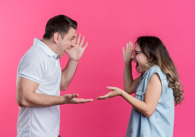 Jong koppel man en vrouw in casual kleding ruzie schreeuwen tegen elkaar over roze