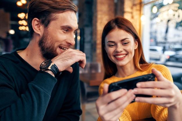 Jong koppel man en vrouw in een restaurant eten bestellen en mobiele telefoon in de hand verlichting
