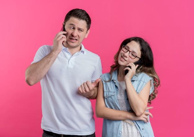 Jong koppel man en vrouw in vrijetijdskleding man praten op mobiele telefoon op zoek verward wijzend op haar vriendin over roze