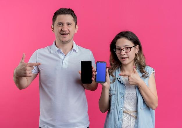 Jong koppel man en vrouw in vrijetijdskleding met smartphones wijzend met vingers naar hen glimlachend over roze
