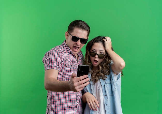 Jong koppel man en vrouw in vrijetijdskleding met zwarte bril kijken naar hun smartphonescherm verrast en verward staande over groene muur