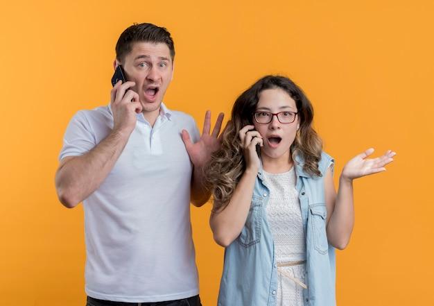 Jong koppel man en vrouw in vrijetijdskleding praten op mobiele telefoons op zoek verward en bezorgd staande over oranje muur