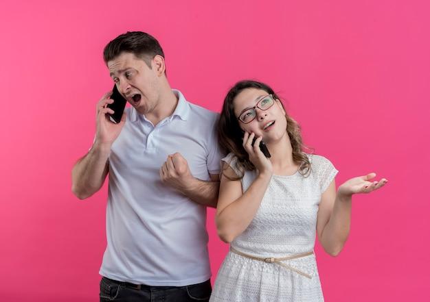 Jong koppel man en vrouw in vrijetijdskleding praten over mobiele telefoons ontevreden en verward staande over roze muur