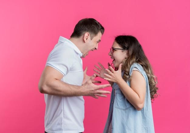 Jong koppel man en vrouw in vrijetijdskleding ruzie schreeuwen tegen elkaar staande over roze muur