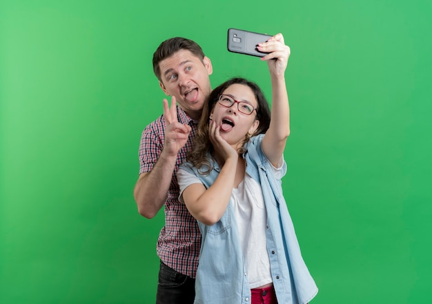 Jong koppel man en vrouw in vrijetijdskleding staan samen selfie gelukkig verliefd plezier over groene muur