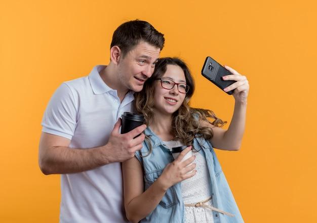 Jong koppel man en vrouw in vrijetijdskleding staan samen selfie gelukkig verliefd plezier over oranje muur
