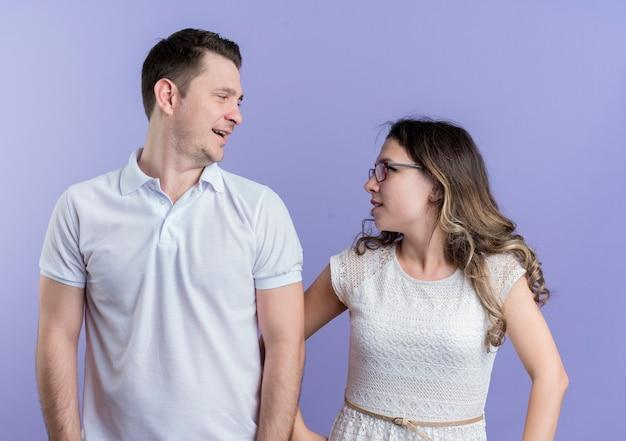 Jong koppel man en vrouw kijken elkaar glimlachend staande over blauwe muur