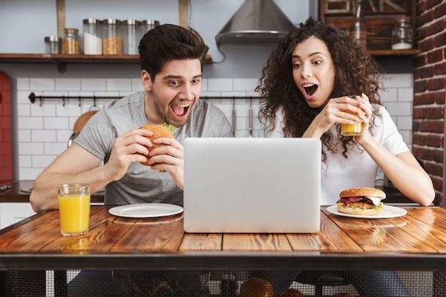 Jong koppel man en vrouw kijken naar laptop op tafel terwijl ze thuis hamburger eten in de keuken