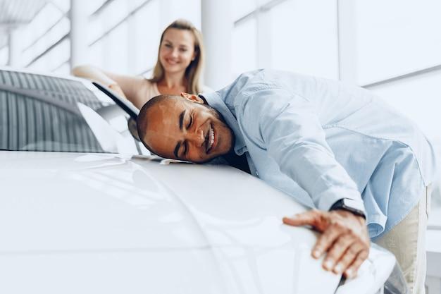 Jong koppel man en vrouw knuffelen hun nieuwe auto in een autowinkel close-up