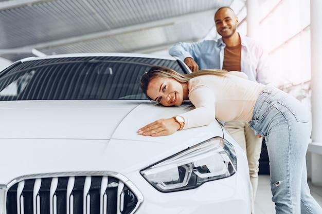 Jong koppel man en vrouw knuffelen hun nieuwe auto in een autowinkel