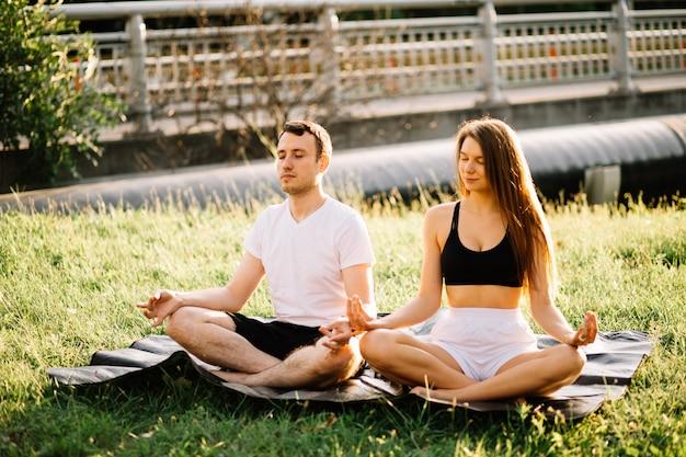Jong koppel man en vrouw mediteren zittend in lotushouding, yoga op stadsgazon, zomeravond samen evening