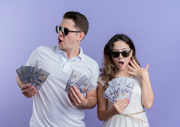 Jong koppel man en vrouw met contant geld blij en opgewonden staande over blauwe muur