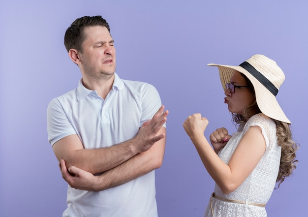 Jong koppel man en vrouw ruzie vrouw met vuisten kijken met boos gezicht naar haar vriendje terwijl hij stopbord toont staande over blauwe muur
