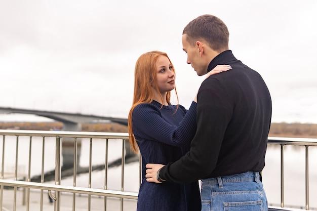 Jong koppel man en vrouw staat knuffelen op de achtergrond van een bewolkte hemel