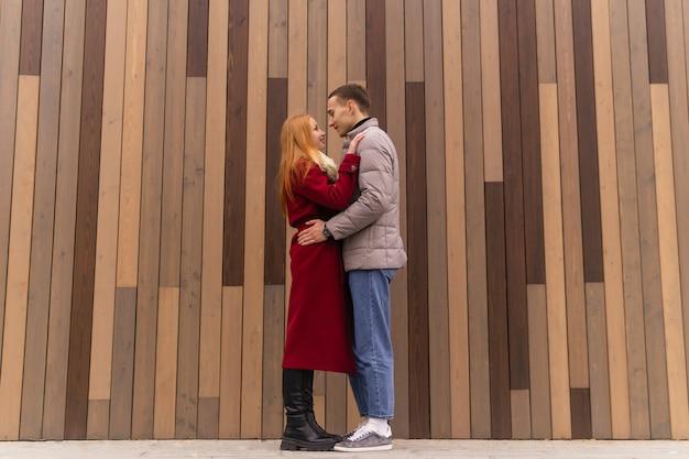 Jong koppel man en vrouw staat knuffelen op de achtergrond van een houten muur