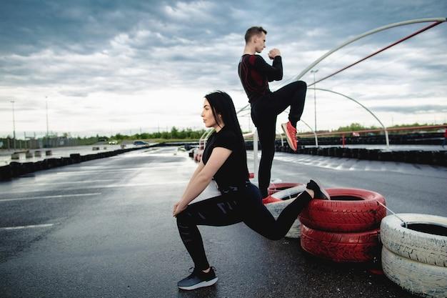 Jong koppel, man en vrouw trainen buitenshuis, strekken been op het sportveld. sport, sporten en lifestyle concept