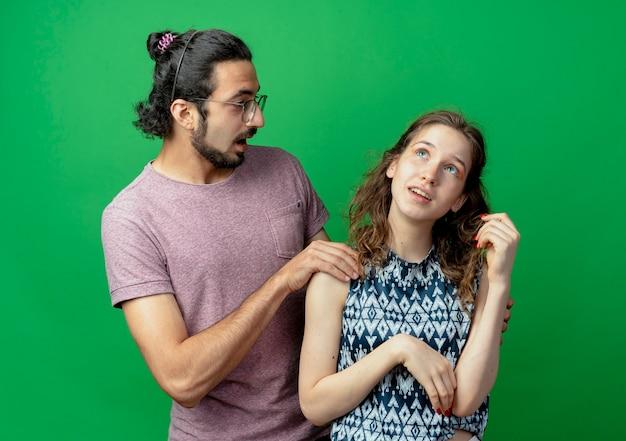 Jong koppel man en vrouw, verrast man schouder van haar vriendin aan te raken die zich met peinzende uitdrukking staande over groene achtergrond