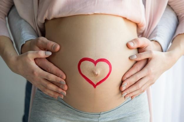 Jong koppel man en vrouw verwachten een baby die thuis samen staat